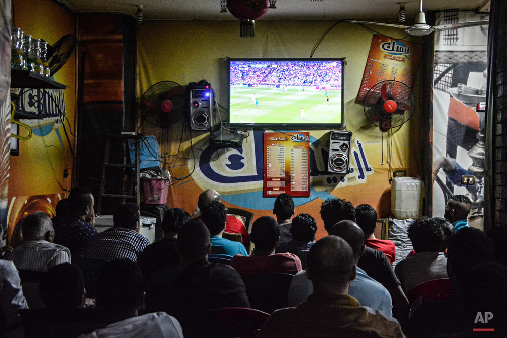 In this May 13, 2015 photo, men watch a soccer match at a local cafe in Cairo, Egypt. Egyptian authorities have banned fans from attending football games, citing ongoing tension between security forces and Ultras groups since a 2012 stadium disaster in Port Said in which at least 72 football fans were killed. (AP Photo/Mohammed El Raai)