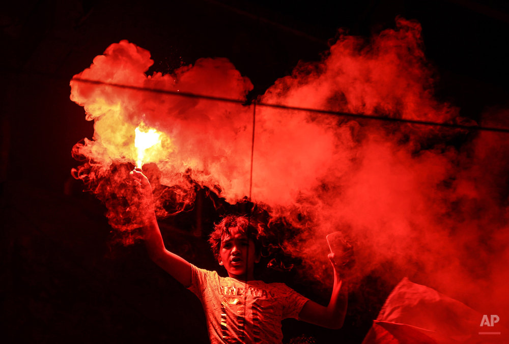 In this July 26, 2015 photo, a member of Zamalek's football club's Ultras White Knights group (UWK), the club's hardcore fan base, lights flares during a friend's bachelor party in Cairo, Egypt. Ultras, whose name comes from the Latin word for ìbeyond,î started in Latin America and Europe in the 1950s and eventually made it to Arab countries, with particularly strong followings in North Africa. The first to form in Egypt, UWK, emerged in 2007 to support the Zamalek team. Groups backing arch-rival al-Ahly and others soon followed. (AP Photo/Mohammed El Raai)