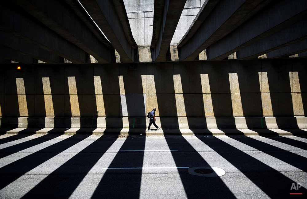 A pedestrian walks through a downtown underpass as the midday sun casts shadows from overhead beams, Thursday, Aug. 7, 2014, in Atlanta. (AP Photo/David Goldman)
