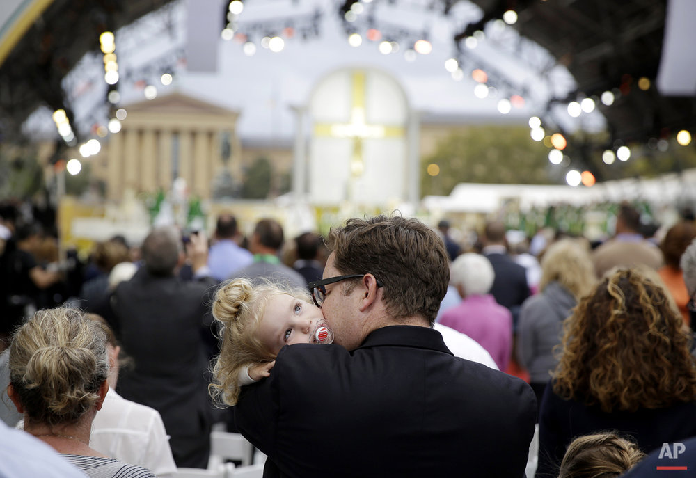 A man holds a child as Pope Francis celebrates Mass, Sunday, Sept. 27, 2015, in Philadelphia. (AP Photo/Matt Slocum)