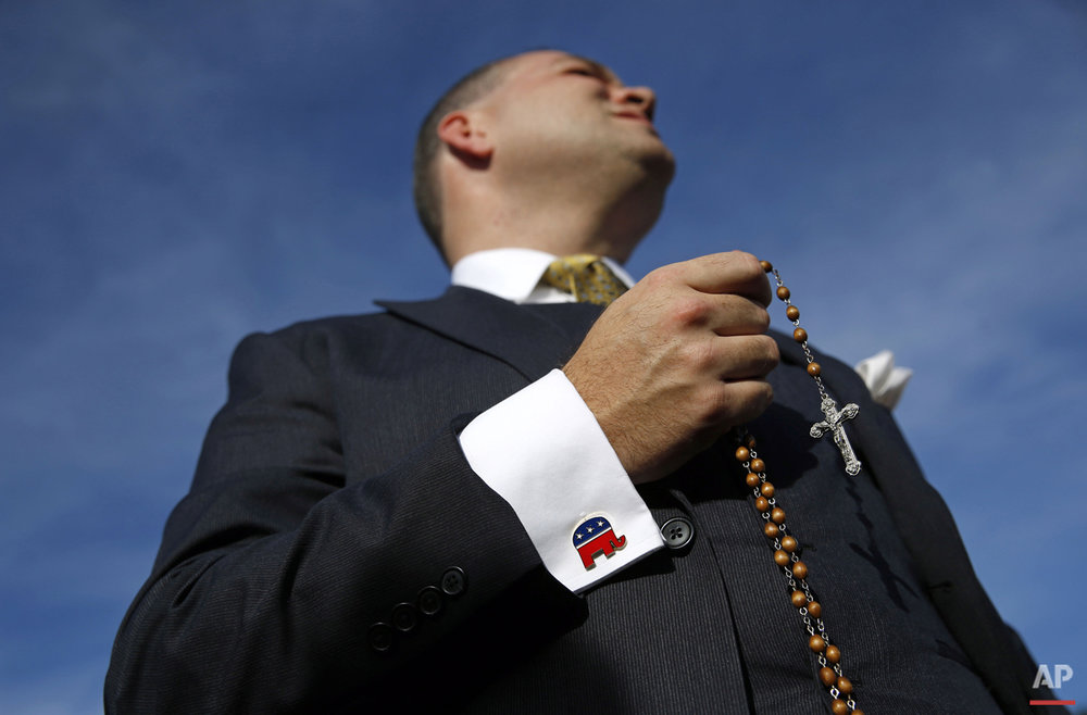 Paul Marich of Woodbridge, Va., prays the rosary as he waits outside the Capitol in Washington, Thursday, Sept. 24, 2015, for a chance to see the Pope Francis after his address to a joint session of Congress. (AP Photo/Patrick Semansky)