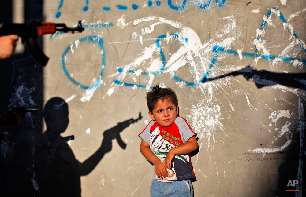A Palestinian boy reacts as youths frighten him by pointing their toy guns at him, in an alley in the West Bank refugee camp of Al-Amari in Ramallah, Tuesday, June. 16, 2009. (AP Photo/Muhammed Muheisen)