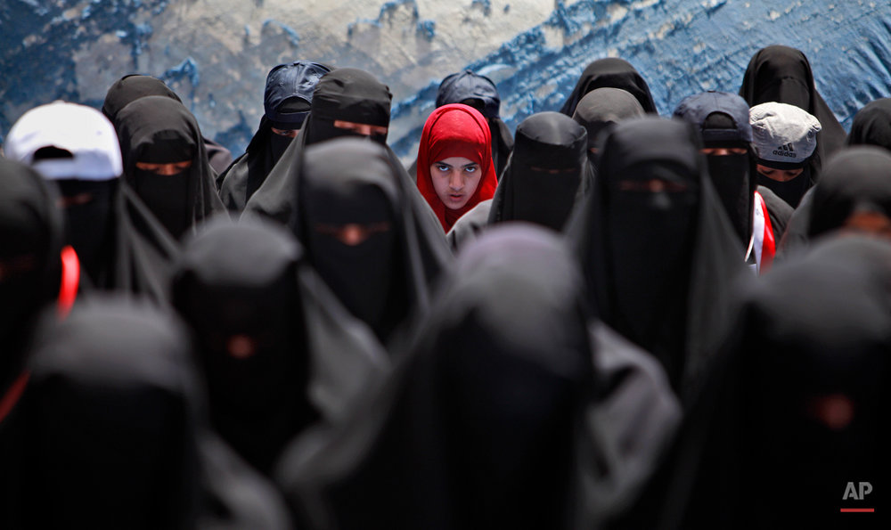 A female anti-government protestor, center, wearing a red scarf, looks on while praying with other women during a demonstration demanding the resignation of Yemeni President Ali Abdullah Saleh, in Sanaa,Yemen, Wednesday, April 6, 2011. Defying a deadly government crackdown, tens of thousands of protesters have poured into the streets of a city in southern Yemen in ongoing protests against longtime president Ali Abdullah Saleh. (AP Photo/Muhammed Muheisen)