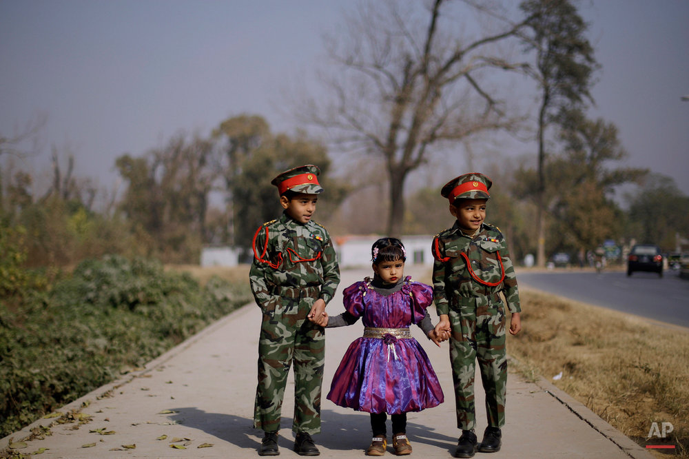 Pakistani Mamouna Qamar, 4, center, looks on while holding her brothers hands, Shazaib, 6, right, and Zaman, 7, as they wait for their parent, unseen, crossing a street in a neighborhood in Islamabad, Pakistan, Friday, Dec. 24, 2010. (AP Photo/Muhammed Muheisen)