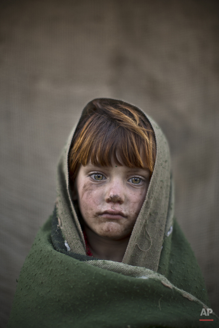 In this Friday, Jan. 24, 2014, photo, Afghan refugee girl, laiba Hazrat, 6, poses for a picture, while playing with other children in a slum on the outskirts of Islamabad, Pakistan. For more than three decades, Pakistan has been home to one of the world's largest refugee communities: hundreds of thousands of Afghans who have fled the repeated wars and fighting their country has undergone.