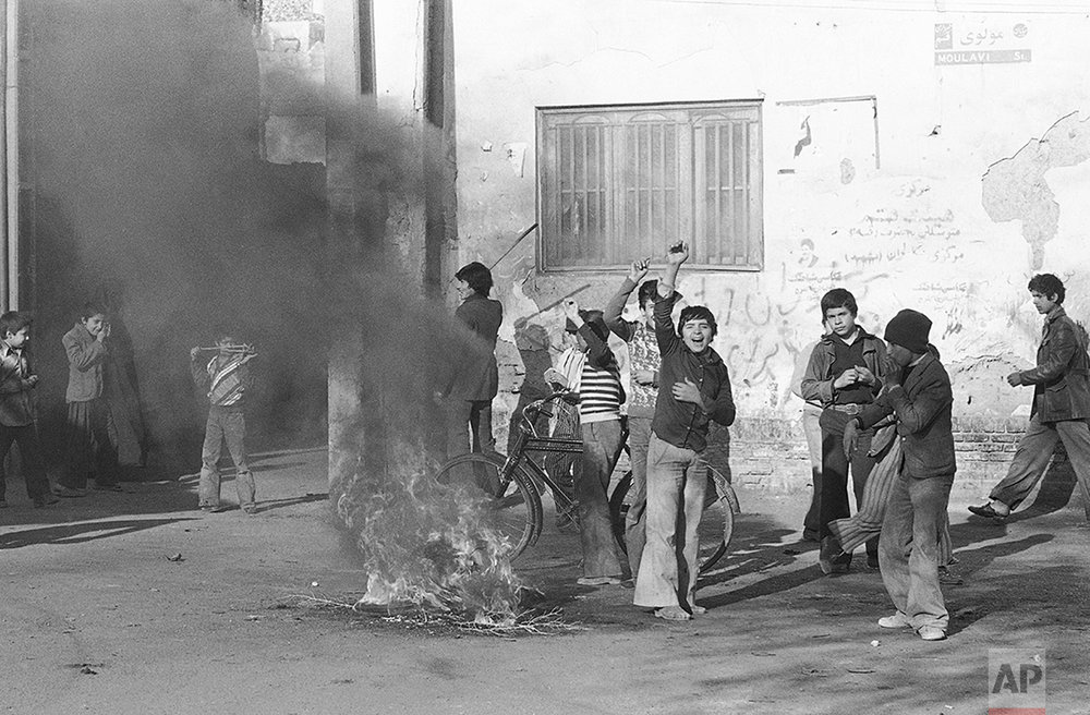 """Teenagers set fire in the streets of the holy city of Qom to mark the """"National Day of Mourning"""" called by exiled Muslim leader Ayatollah Khomeini in memory of those killed in recent clashes with military, Dec. 18, 1978. Several people were wounded in renewed outbreaks of violence in Tehran. (AP Photo/Michel Lipchitz)"""