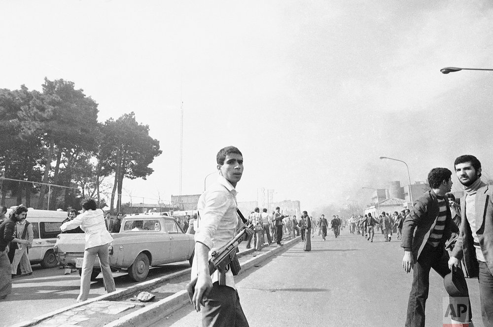 A supporter of Ayatollah Khomeini stands on Saturday, Feb. 10, 1979 at Tehran Street, holding an M16 rifle. Hospitals reported 62 dead and more than 300 wounded as troops battled dissident air force cadets and armed civilian supporters of Khomeini. (AP Photo)