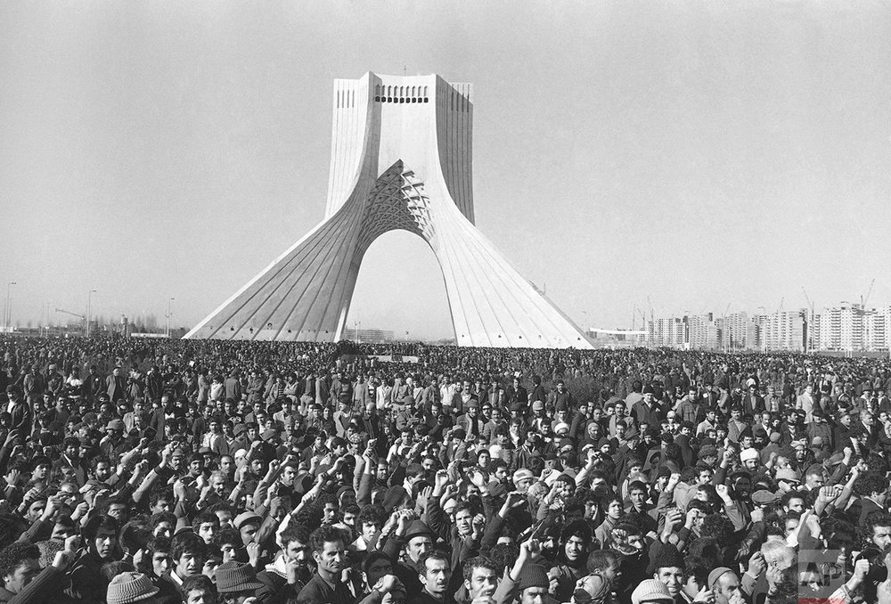 """Hundreds of thousands are gathered around Shayad Arch, on Saturday, Jan. 27, 1979 in Tehran on the traditional anniversary of the Prophet Mohammad death to demand the return of religious leader Ayatollah Khomeini. The demonstrators, marching through Tehran streets, chanted slogans in praise of Khomeini whose return from 14 years exile was delayed by the government, and the crowd shouted also """"death to Bakhtiar, if Khomeini is delayed."""" (AP Photo/Dear)"""