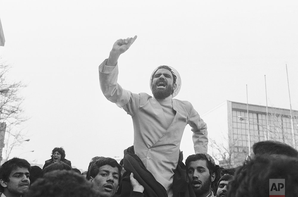 A mullah rides on the shoulders of rioters in Tehran, gesticulates as he tries to calm the mob that chased a traffic policeman to beat him up, Jan. 30, 1979. The policeman escaped into a house. (AP Photo/Bob Dear)