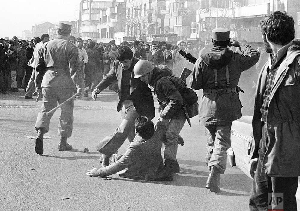 A demonstrator clubbed down by a stick wielding army officer (left) during one of the skirmishes between demonstrators and the army downtown, on Sunday, Jan. 14, 1979 in Tehran is helped up by a steel-helmeted soldier. Soldiers had orders to use clubs instead of their guns when dealing with the demonstrators. (AP Photo/Aristotle Saris)