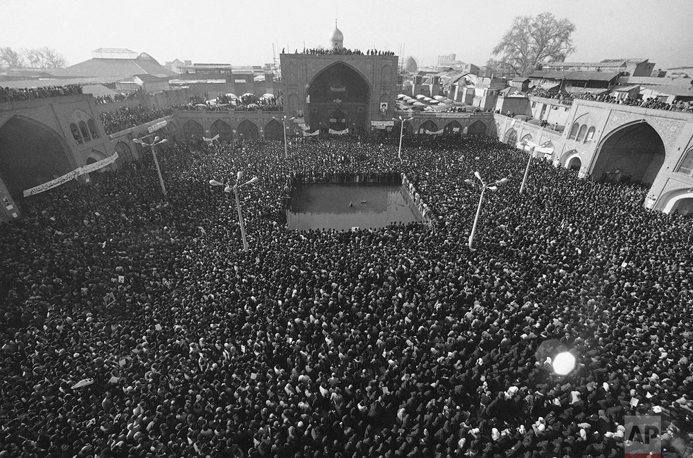 """Chanting """"Long Live Khomeini"""" and """"Death to the Shah,"""" 100,000 people gather in front of the mosque inside the Bazaar on Monday, Jan. 15, 1979 in Tehran for a massive rally against the Shah. Troops stood by as demonstrators showered them with flowers, and kisses. (AP Photo)"""