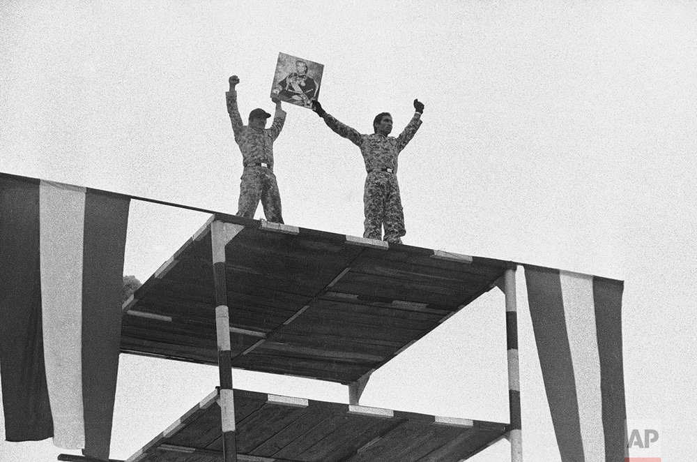 """Two Iranian soldiers hold up a portrait of the Shah, as the army shows its strength in Tehran on a parade ground near Niavaran Palace, Jan. 23, 1979. Officers asserted that the army will stay united and that soldiers will """"shed their blood"""" to maintain the monarchy and the nation's civilian government. (AP Photo/Aristotle Saris)"""