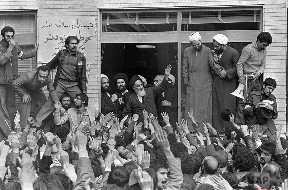 Islamic Fundamentalist cleric Ayatollah Ruhollah Khomeini, center, waves to followers as he appears on the balcony of his headquarters in Tehran, Iran, on Friday, Feb. 2, 1979, the second day of his return from exile. Thousands jammed surrounding streets to get a view of the Ayatollah. (AP Photo/Campion)