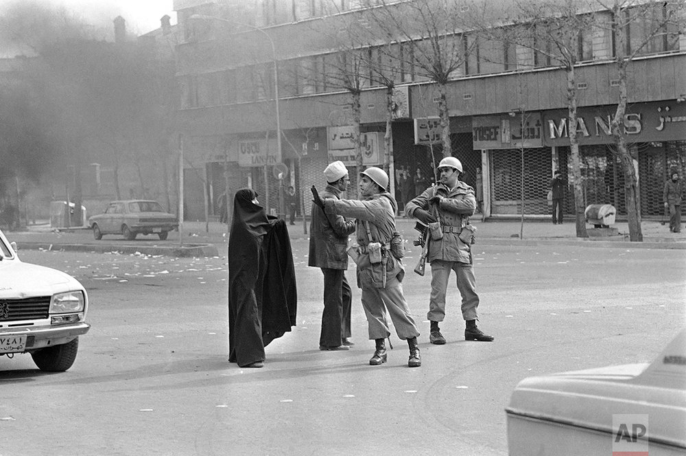 A Muslim couple appeals to Iranian soldiers in downtown Tehran, on Friday, Jan. 26, 1979 to stop firing at demonstrators, but they were stopped by the gesticulating unit commander. At least five persons were killed and several wounded, when they army fired sharp rounds to quell the riots. (AP Photo/ Bob Dear)