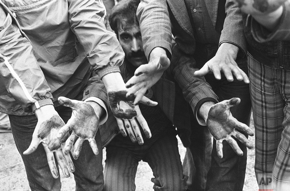 Demonstrators show their hands that they had dipped into the blood of friends who were wounded or killed when anti-government rioters clashed with the army in downtown streets in Tehran, Jan. 26, 1979. At least ten demonstrators were killed by bullets, and several injured, when the army used sharp rounds to quell the riots. (AP Photo/Bernhard Frye)