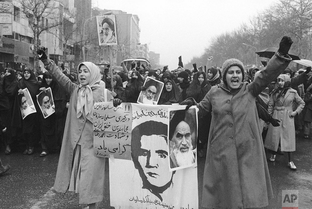 """A young Muslim woman chants """"God is great"""" while carrying portraits of religious leader Ayatollah Khomeini and a young urban guerilla who was killed in a street battle with security forces, during demonstrations on Jan. 22, 1979 in Tehran. (AP Photo/Aristotle Saris)"""