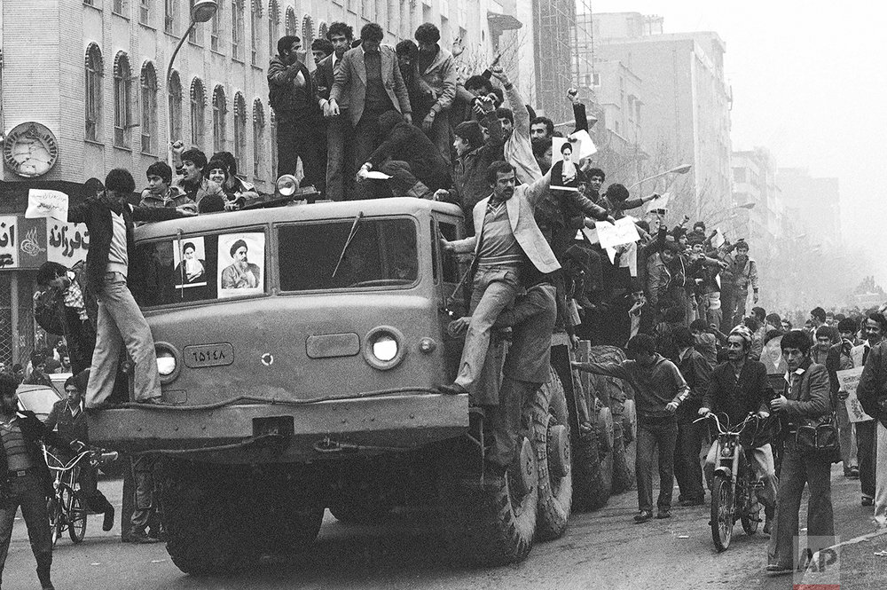 Dozens of demonstrators who have invaded an Iranian army truck, downtown on Wednesday, Jan. 17, 1979 in Tehran proceed in their joyful demonstration on the second day after the Shah's departure. Again hundreds were in the streets, clanking their horns and decorating the cars windshields with pictures of religious leader Ayatollah Khomeini. (AP Photo/Saris)