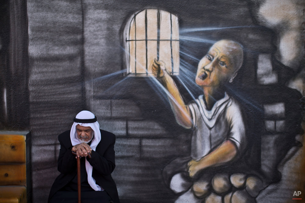 "In this Monday, June 16, 2014 photo, Palestinian refugee Shaher Alkhateeb, 73, who witnessed  what the Palestinians call the ""Nakba,"" or ìcatastropheî referring to their uprooting in the war over Israel's 1948 creation, poses for a picture in front of a wall painted with a mural depicting a prisoner jailed in Israel, in Kalandia refugee camp, between Jerusalem and the West Bank city of Ramallah. Alkhateeb was 6 years old when he and other 7 members of his family were forced to leave their village of Al-Burj, near the central Israeli town of Ramla and took shelter with his family in the Kalandia refugee camp. (AP Photo/Muhammed Muheisen)"
