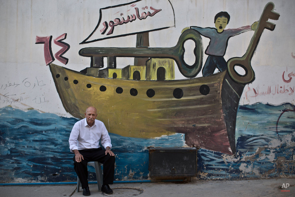 In this Tuesday, June 17, 2014 photo, Palestinian refugee Abduljalil Al-Noursi, 70, poses for a picture in front of a wall painted with a mural showing a ship and the words ìwe will returnî written on the sail, in the West Bank refugee camp of Jenin. In Palestinian refugee art, a ship is a common symbol of the hopes of return. Al-Nursi was four years old when he and 19 relatives fled with just the clothes on their backs during the the Mideast war over Israel's 1948 creation. ìI won't let go of my right of return,î he said.(AP Photo/Muhammed Muheisen)