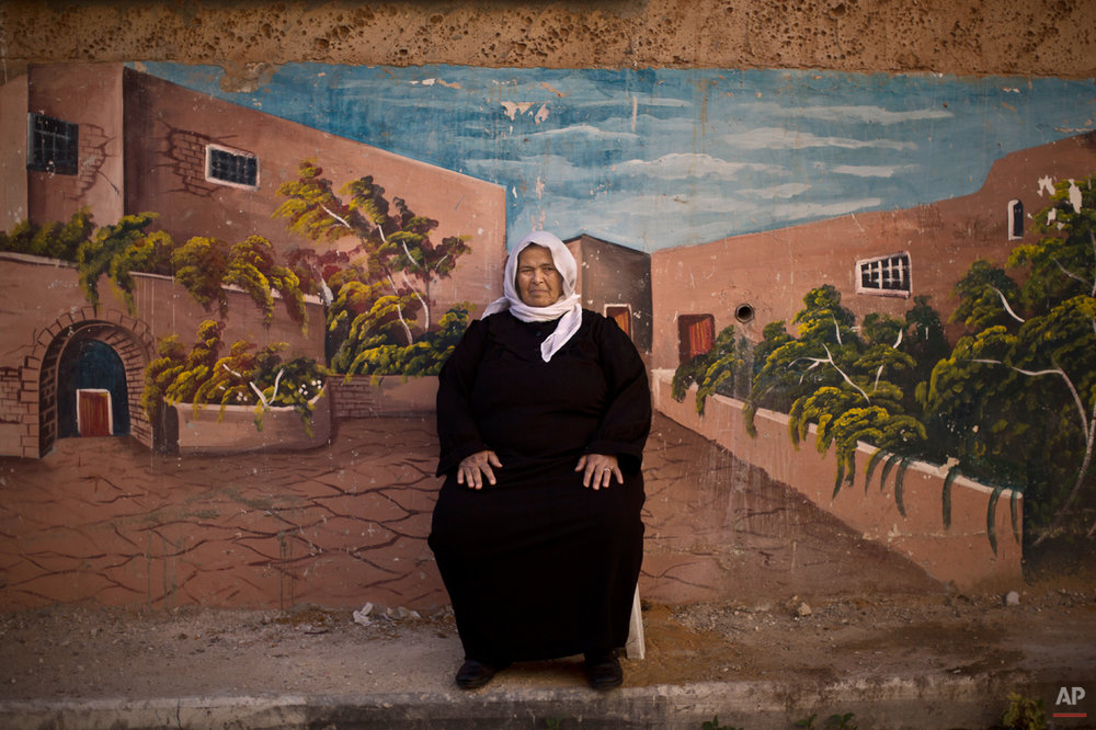 In this Tuesday, June 17, 2014 photo, Palestinian refugee Jamilah Shalabi, 70, poses for a picture in front of a wall painted with a mural in the West Bank refugee camp of Jenin, where she has lived since she was 4 years old when she and her parents were forced to leave their home in Zarin village, near the in the northern Israeli town of Beit Shean. More than 700,000 Palestinians fled or were driven out in the 1948 Mideast war, according to U.N. figures. (AP Photo/Muhammed Muheisen)