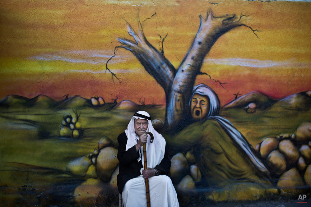 In this Wednesday, June 18, 2014 photo, Palestinian refugee Mohammed Emtair, 85, poses for a picture in front of a mural depicting the Israeli-Palestinian conflict, in the Kalandia refugee camp between Jerusalem and the West Bank city of Ramallah. The United Nations refugee agency says that at the end of last year, more than 50 million people have been forced from their homes worldwide, the highest figure of displaced since World War II. (AP Photo/Muhammed Muheisen)
