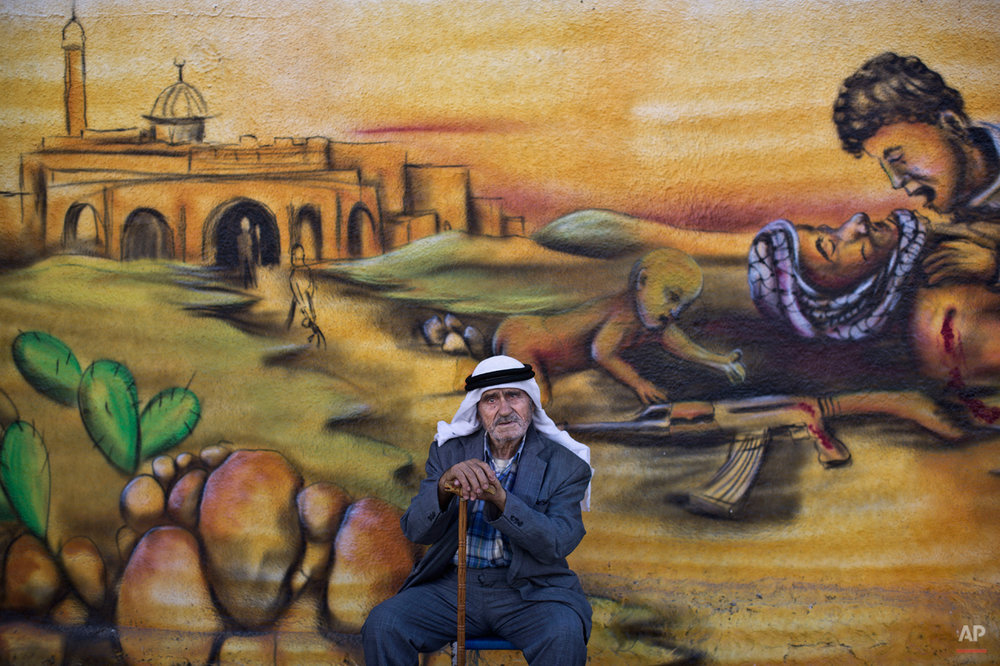 "In this Wednesday, June 18, 2014 photo, Palestinian refugee Abdul Ghafour Abdulrahman, 85, who witnessed  what the Palestinians call the ""Nakba,"" or ìcatastropheî referring to their uprooting in the war over Israel's 1948 creation, poses for a picture in front of a wall painted with a mural depicting the Israeli-Palestinian conflict in the Kalandia refugee camp, between Jerusalem and the West Bank city of Ramallah. Today, those who were uprooted and their descendants number more than 5 million people, scattered across the West Bank, Gaza Strip, Jordan, Syria and Lebanon.(AP Photo/Muhammed Muheisen)"