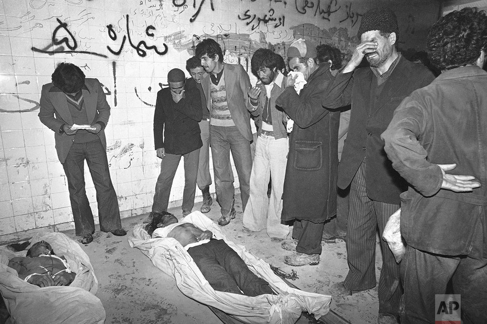 Relatives stand in the morgue of Behesht Zahra, Tehran's main public cemetery, on Sunday, Jan. 28, 1979 lamenting two of the victims of recent riots. Friday and Sunday brought back the days of the bloodiest riots with a death toll of about 30 in Tehran, Iran Sunday, and more than 200 wounded. (AP Photo/Saris)
