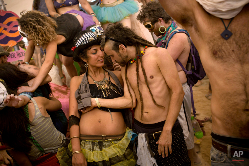 In this photo taken Thursday, June 5, 2014, Israelis dance at a party during Israelís first Midburn festival, modeled after the popular Burning Man festival held annually in the Black Rock Desert of Nevada, in the desert near the Israeli kibbutz of Sde Boker. Some came costumed in cape or corset. Others, from babies to grandparents, went nude. Participants brought their own food and water, and shared with others. The only thing on sale was ice because of the scorching heat. There were workshops in sculpture, drawing, and touch therapy. There was music and theater. At the ìtent of heaven and hell,î participants were chosen at random for one of two fates: getting massages or doing chores. (AP Photo/Oded Balilty)