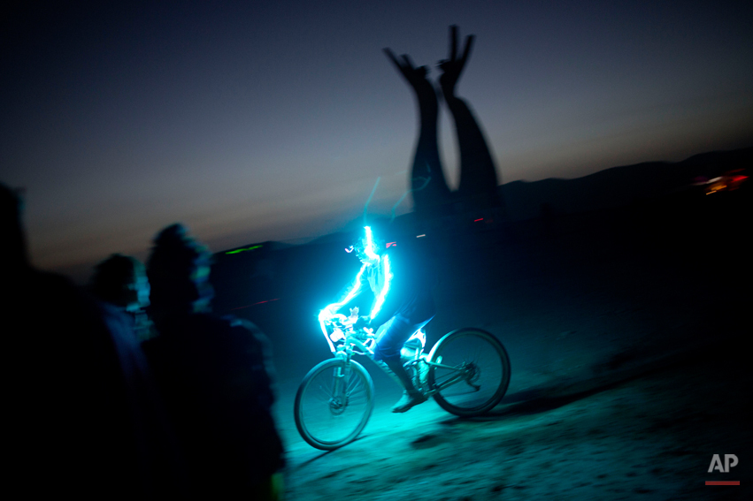 In this photo taken Thursday, June 5, 2014, An Israeli man rides a bicycle as the sun goes down during Israelís first Midburn festival, modeled after the popular Burning Man festival held annually in the Black Rock Desert of Nevada, in the desert near the Israeli kibbutz of Sde Boker. For five days, participants _ mostly Israelis _ created a temporary city dedicated to creativity, communal living and what the festival calls ìradical self-expression.î (AP Photo/Oded Balilty)