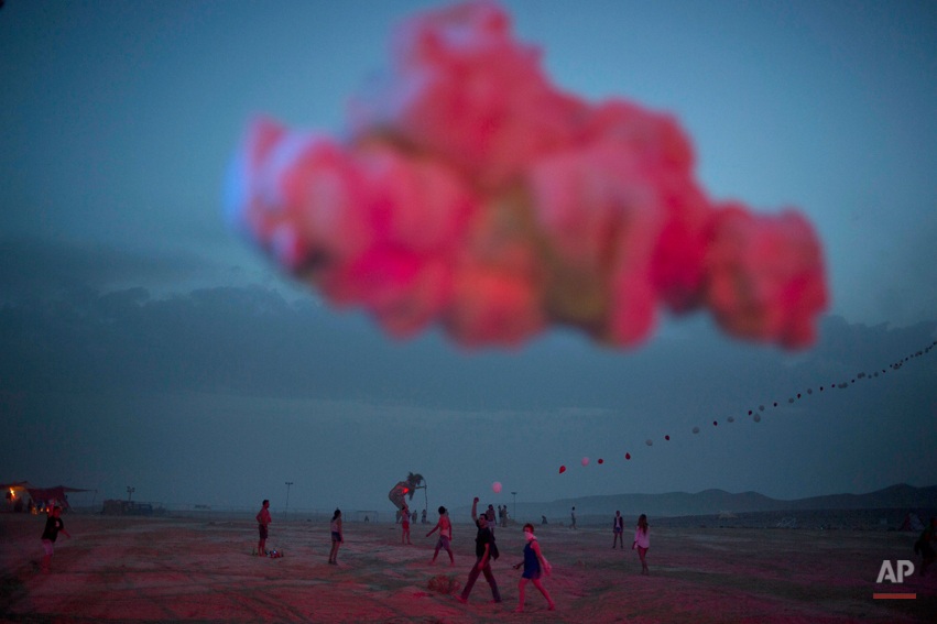 In this photo taken Wednesday, June 4, 2014, Israelis walk in the playa during the Israelís first Midburn festival, modeled after the popular Burning Man festival held annually in the Black Rock Desert of Nevada, in the desert near the Israeli kibbutz of Sde Boker. Some 3,000 people set up a colorful encampment in the dusty moonscape, swinging from hoops by day and burning giant wooden sculptures by night. (AP Photo/Oded Balilty)
