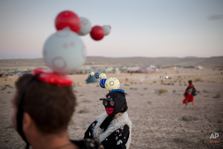 In this photo taken Friday, June 6, 2014, Israelis in costumes walk around the playa during Israelís first Midburn festival, modeled after the popular Burning Man festival held annually in the Black Rock Desert of Nevada, in the desert near the Israeli kibbutz of Sde Boker. For the Bedouin Arab shepherds tending their flocks in Israelís Negev desert last week, it was almost as if aliens had landed from outer space. (AP Photo/Oded Balilty)