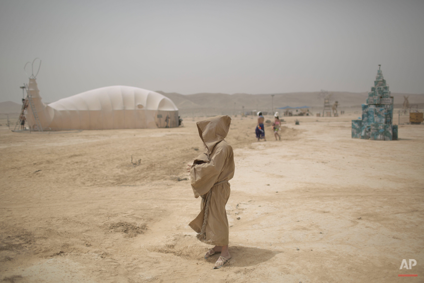 In this photo taken Wednesday, June 4, 2014, an Israeli man walks in the playa during Israelís first Midburn festival, modeled after the popular Burning Man festival held annually in the Black Rock Desert of Nevada, in the desert near the Israeli kibbutz of Sde Boker. Some 3,000 people set up a colorful encampment in the dusty moonscape, swinging from hoops by day and burning giant wooden sculptures by night. (AP Photo/Oded Balilty)