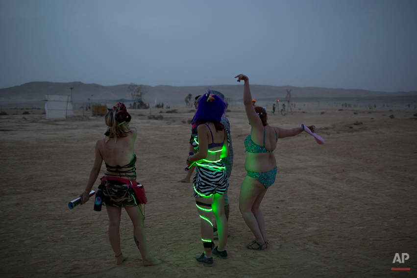 "In this photo taken Wednesday, June 4, 2014, Israelis dance at a party during Israelís first Midburn festival, modeled after the popular Burning Man festival held annually in the Black Rock Desert of Nevada, in the desert near the Israeli kibbutz of Sde Boker. Some 3,000 people set up a colorful encampment in the dusty moonscape, swinging from hoops by day and burning giant wooden sculptures by night. For five days, participants mostly Israelis created a temporary city dedicated to creativity, communal living, and what the festival calls ìradical self-expression"". (AP Photo/Oded Balilty)"