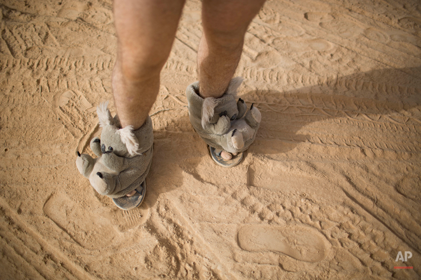 "In this photo taken Thursday, June 5, 2014, an Israeli man walks in house slippers during Israelís first Midburn festival, modeled after the popular Burning Man festival held annually in the Black Rock Desert of Nevada, in the desert near the Israeli kibbutz of Sde Boker. For five days, participants mostly Israelis created a temporary city dedicated to creativity, communal living, and what the festival calls ìradical self-expression.""(AP Photo/Oded Balilty)"