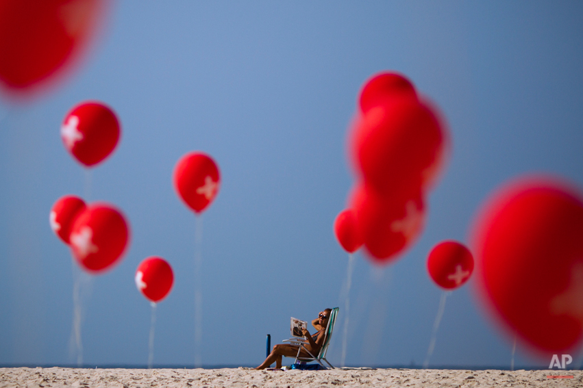 A woman sunbathes next to a demonstration organized by firefighters demanding a wage increase, on Copacabana beach in Rio de Janeiro, Brazil, Sunday June 12, 2011. Organizers brought 439 red balloons representing the number of firemen who were arrested after days of protests ended with the occupation of the fire brigade headquarters last week. The firemen were eventually released. (AP Photo/Felipe Dana)