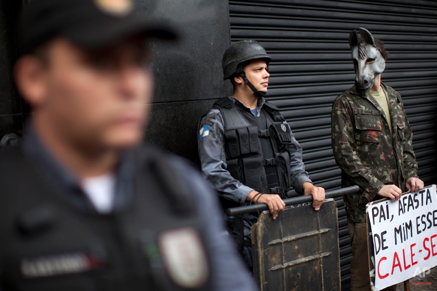 "An activist wearing a donkey mask stands next to police as they stand guard outside a military club during a protest in downtown Rio de Janeiro, Brazil, Thursday March 29, 2012. A club of retired military officers held its annual celebration of Brazil's 1964 military coup as usual, but faced protestors as members arrived for the event. Unlike its Latin American neighbors, Brazil never had a formal investigation into its 20-year dictatorship. The sign reads in Portuguese "" Father keep that one awayÖshut-up,"" a play on words from a song by famous singer Chico Buarque which was censored during the dictatorship. (AP Photo/Felipe Dana)"