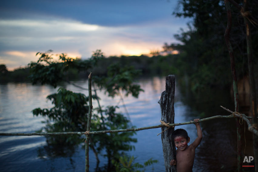 An indigenous boy plays near the Rio Negro river during sunset in the Tatuyo indigenous community, near Manaus, Brazil, Monday, May 19, 2014. Manaus is one of the host cities for the 2014 World Cup in Brazil. (AP Photo/Felipe Dana)