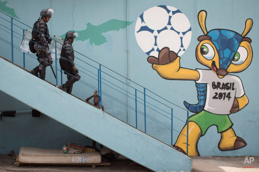 Riot police walk next to a mural of the mascot for the 2014 World Cup soccer tournament, called Fuleco, near the Maracana stadium, after evicting Indians from the nearby old Indian Museum in Rio de Janeiro, Friday, March 22, 2013. Police in riot gear invaded an old Indian museum complex Friday and pulled out a few dozen indigenous people who for months resisted eviction from the building, which will be razed as part of World Cup preparations next to the legendary Maracana football stadium. (AP Photo/Felipe Dana)