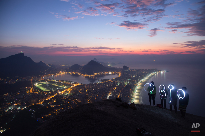 For this photo captured using a long exposure, a group of friends asked the photographer to take their picture as they used flashlights to paint with light, a heart symbol and the word 'Rio' while standing at the apex of Morro Dois Irmaos or Two Brothers Mountain at dawn, in Rio de Janeiro, Brazil, Saturday, May 17, 2014. (AP Photo/Felipe Dana)