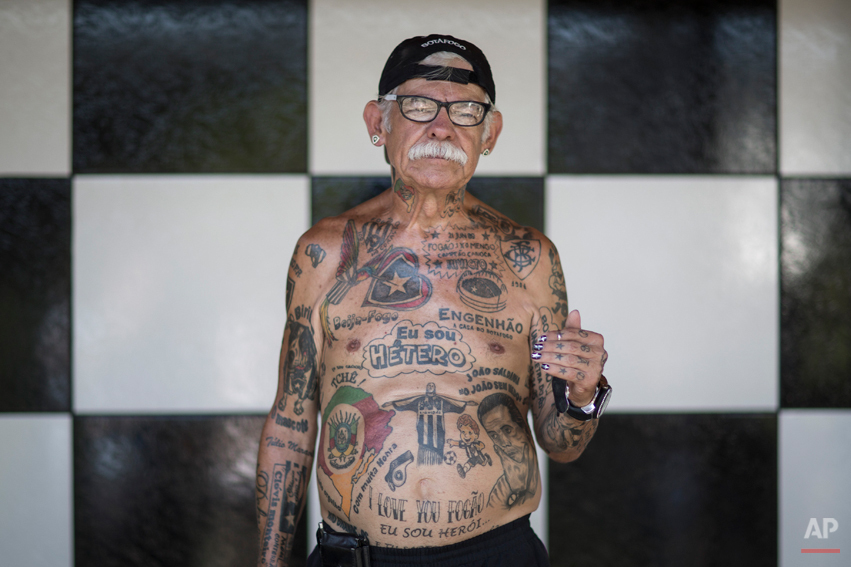 In this May 8, 2014 photo, soccer fan Delneri Viana, 69, poses for a photo in his home, decorated with Botafogo colors in Rio de Janeiro, Brazil. Aside from the 83 and counting tattoos, the gray-haired man with a full, chalky mustache sports finger and toe nails painted in his teamís black and white colors. In fact, he never wears anything without the clubís emblem.(AP Photo/Felipe Dana)