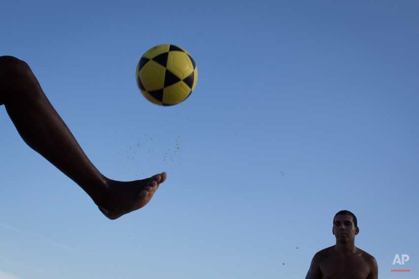 A man controls the ball with his foot while playing 'altinho' on the Ipanema beach in Rio de Janeiro, Brazil, Saturday, May 31, 2014. Altinho is a popular local game that is played with a soccer ball on the beach. The goal is not to let the ball drop, but passing to other players while keeping it airborne. The international soccer tournament is set to begin in just a few weeks, with Brazil and Croatia competing in the opening match on June 12. (AP Photo/Felipe Dana)