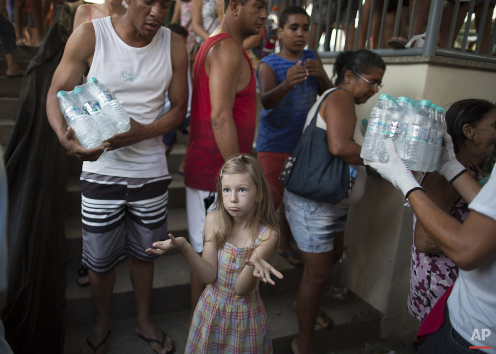In this Nov. 21, 2015 photo, a girl questions why the man standing next to her was allowed to step ahead of her in a line for free water, at a distribution site, in Colatina, Brazil. Residents were queuing day and night for the bottles of water. (AP Photo/Leo Correa)