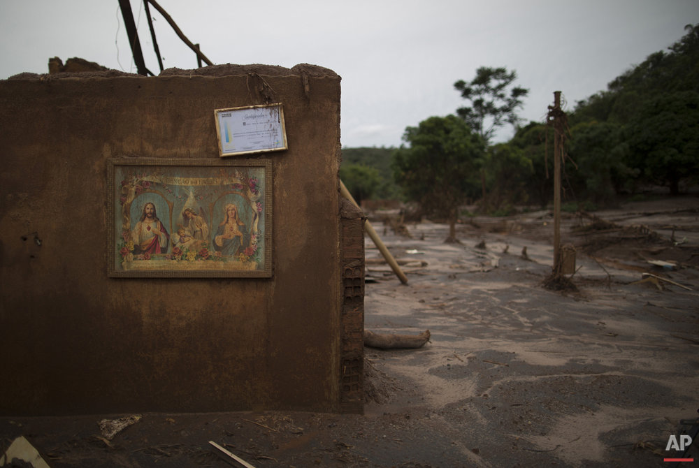 "In this Nov. 24, 2015 photo, a framed military police certificate hangs above a framed image of Jesus Christ and Mary with a message that reads in Portuguese ""Blessing of the homes,"" hang on the wall of a home destroyed by an early November mudslide, in Paracatu, Brazil. Then the dam at a nearby iron ore mine burst, it unleashed a tsunami of mud that swept away nearly everything in its path, flattening houses, uprooting trees and tossing cars asunder. (AP Photo/Leo Correa)"