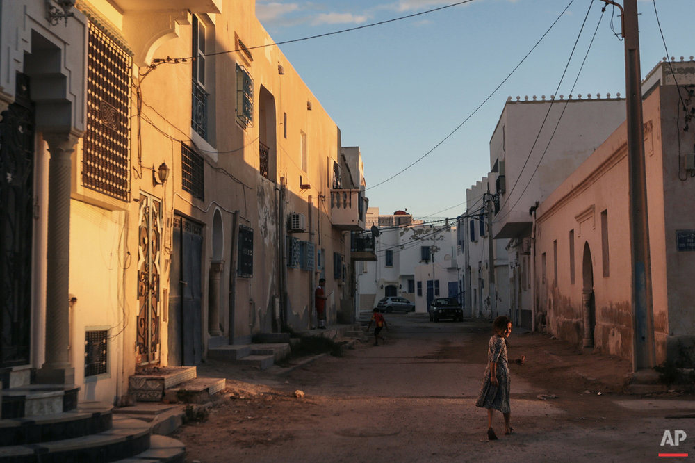 In this Friday, Oct. 30, 2015 photo, a girl walks home after sunset, at Hara Kbira, the main Jewish neighbourhood on the Island of Djerba, southern Tunisia. The Jewish community in the resort island of Djerba traces its roots all the way back to Babylonian exile of 586 B.C., and is one of the few communities of its kind to have survived the turmoil around the creation of Israel, when more than 800,000 Jews across the Arab world either emigrated or were driven from their homes. (AP Photo/Mosa'ab Elshamy)