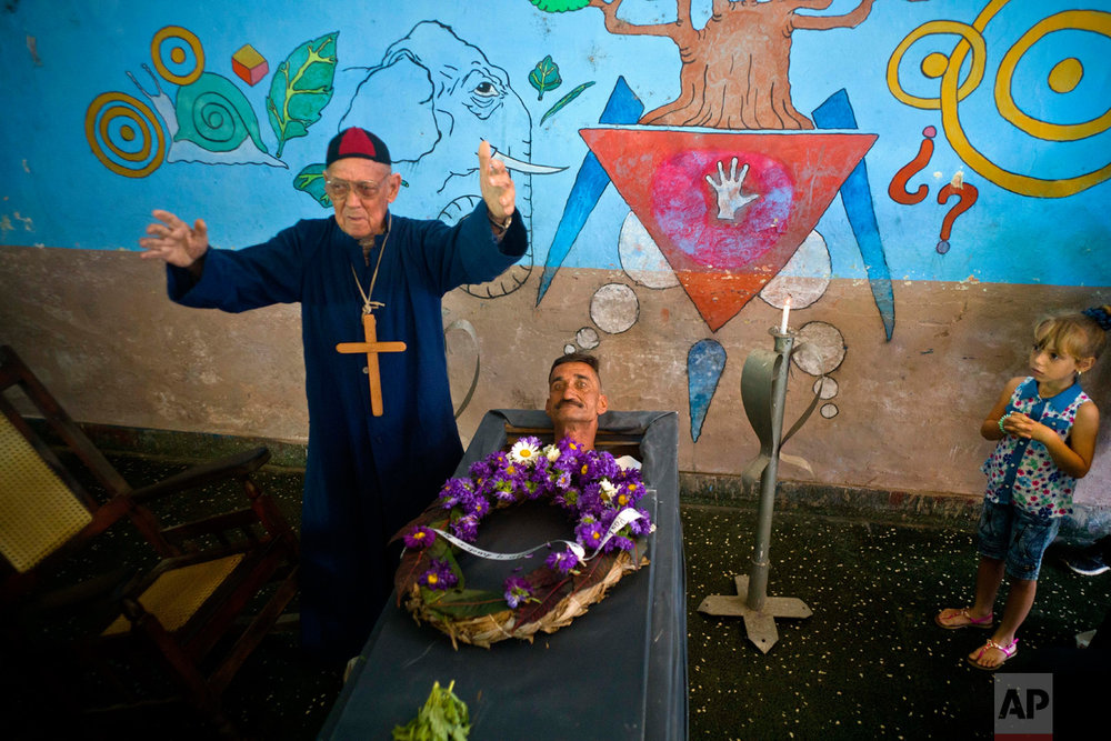 Marcelino Rogelio Estrada performs the role of a priest during the annual celebration known as the Burial of Pachencho, played by Divaldo Aguiar, who lies in a coffin during the mock funeral service, in Santiago de Las Vegas, Cuba, Sunday, Feb. 5, 2017. Residents stage the mock funeral and burial of Pachencho in a boozy festival that has become an annual tradition to mark the end of the local carnival season. (AP Photo/Ramon Espinosa)