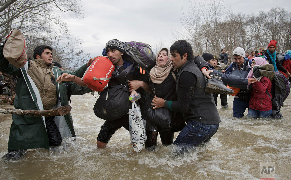 A woman is supported by two men while crossing a river as migrants attempt to reach Macedonia on a route that would bypass the border fence, Monday, March 14, 2016. Hundreds of migrants and refugees walked out of an overcrowded camp on the Greek-Macedonian border Monday, determined to use a dangerous crossing to head north. AP photographer Vadim Ghirda of Romania won second prize in the Contemporary Issues - Singles category in the 2017 World Press Photo competition with an emotionally charged photo of migrants crossing a river as they attempt to reach Macedonia.  (AP Photo/Vadim Ghirda)