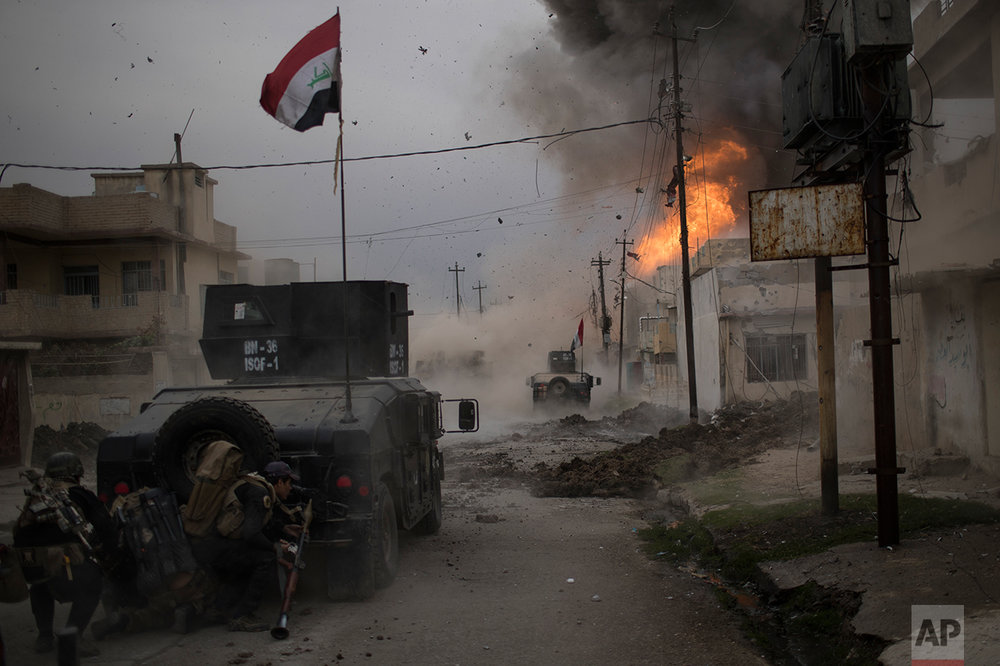 A car bomb explodes next to Iraqi special forces armored vehicles as they advance towards Islamic State held territory in Mosul, Iraq, Wednesday, Nov. 16, 2016.  AP photographer, Felipe Dana, came third in the Spot News - Singles category in the 2017 World Press Photo competition for his image of an explosion in Mosul.  (AP Photo/Felipe Dana)