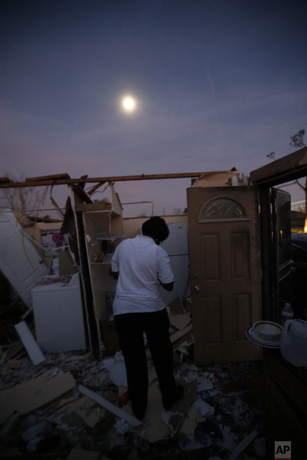 With a moon rising overhead, Theresa Perkins retrieves some belongings from inside of the destroyed home of her friend, Thelma Packnett, in the aftermath of Tuesday's tornado that tore through the New Orleans East section of New Orleans, Wednesday, Feb. 8, 2017. (AP Photo/Gerald Herbert)