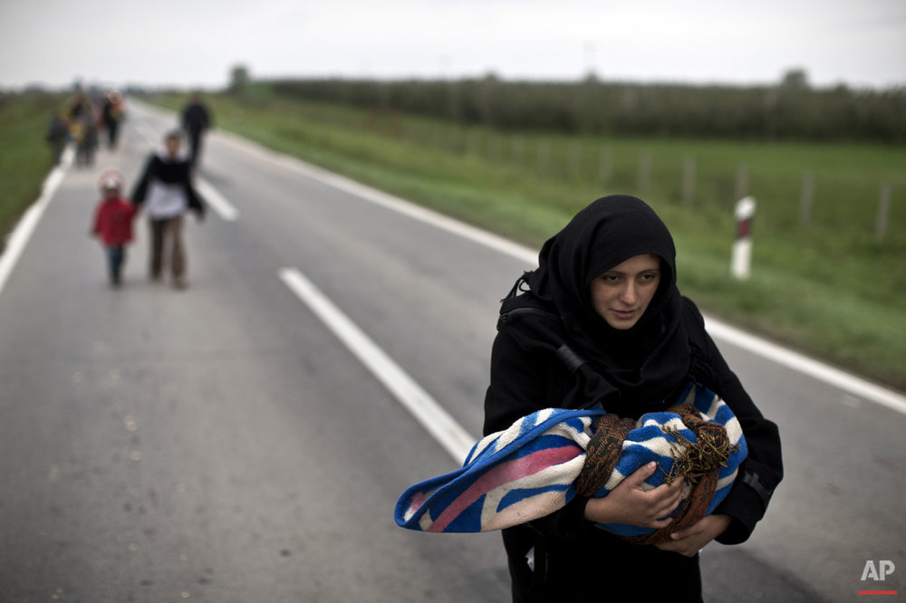 A woman carries a child as she moves on foot towards a registration center in Opatovac, Croatia, Tuesday, Oct. 20, 2015. (AP Photo/Marko Drobnjakovic)