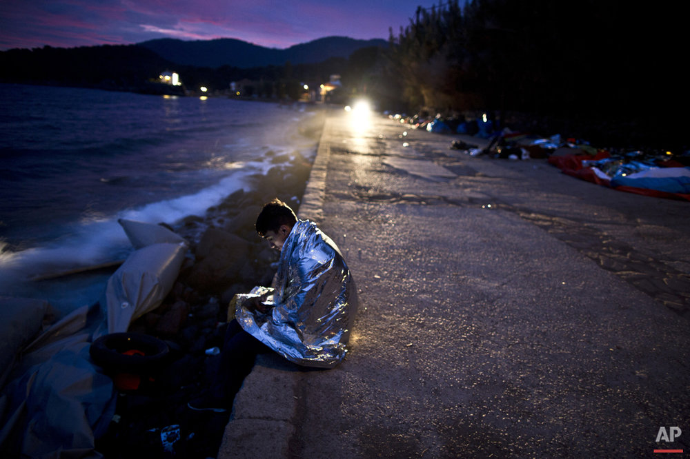An Afghan refugee wrapped, in a thermal blanket faces the sea after he and others arrived late in the night on a dinghy from the Turkish coast to the northeastern Greek island of Lesbos, early Thursday, Oct. 8 , 2015. (AP Photo/Muhammed Muheisen)